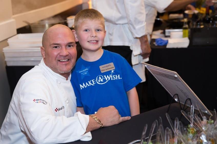 Chef Miguel Blasini and child at a delicious wishes event