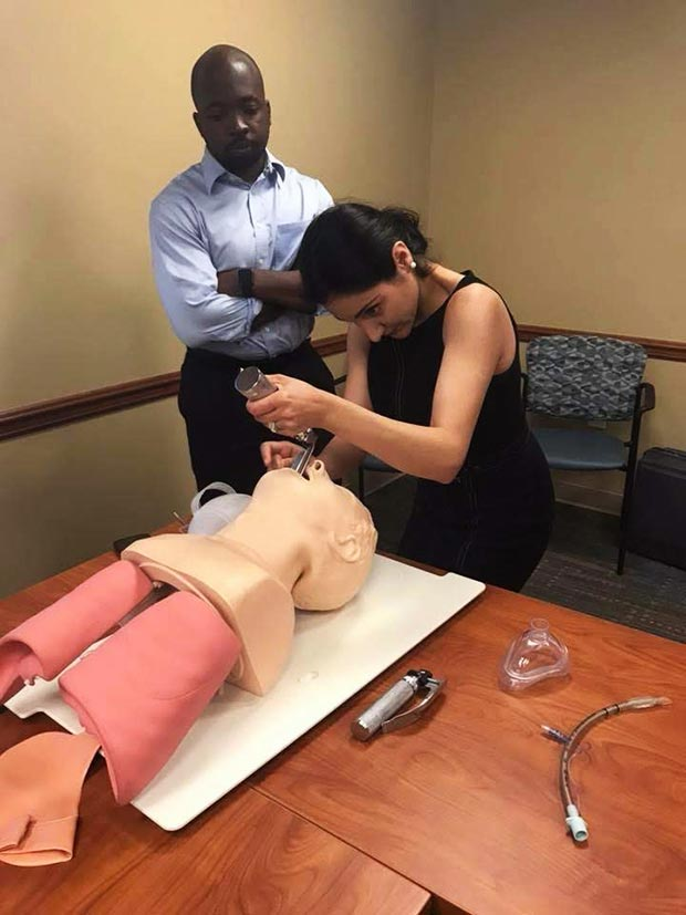 a resident practices intubation on a practice dummy while an instructor watches